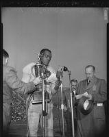Kenny Washington receives a football award