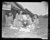 Four American Indian girls playing with dolls and tea set at a tent city in Calif., circa 1951