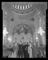 Clergy, civic leaders and artist standing in nave with dome and Iconostasis behind them during opening of St. Sophia Greek Orthodox Cathedral in Los Angeles, 1952