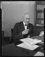 Judge Thomas L. Ambrose, seated in his study.