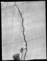 Man pointing at crack in Saint Francis Dam after its collapse, San Francisquito Canyon, 1928