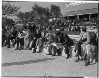 Spectators read the paper at the Santa Anita racetrack, February 22, 1937.