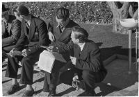 Spectators check their betting sheet on opening day of Santa Anita's fourth horse racing season, Arcadia, December 25, 1937