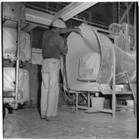 Employee sprays a new ceramic sink with a hose at the Universal Vitreous China Factory, Mentone, circa 1948