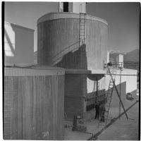 Three men stand outside the Universal Vitreous China Factory, Mentone, circa 1948