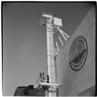 Three men stand on a platform outside the Universal Vitreous China Factory, Mentone, circa 1948